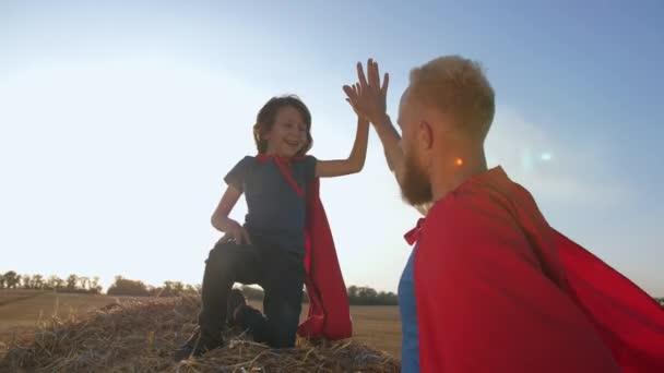 Örömteli fiú és apa úgy tesz, mintha a szuperhősök