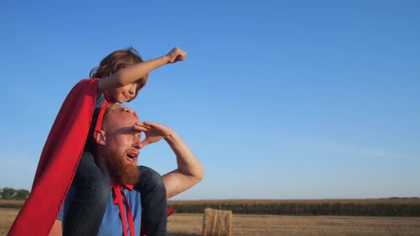 Papà cammina con il figlio sulle spalle attraverso il campo