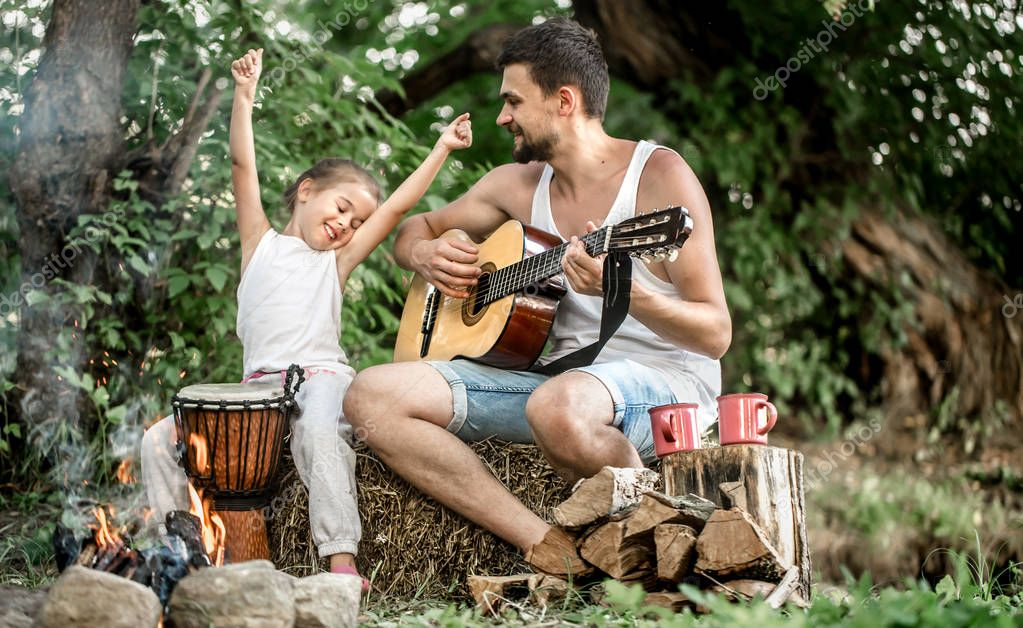 Dad's family camping plays guitar to his daughter in nature, the concept of family values and pastime