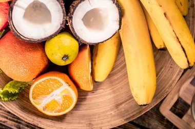 Fresh different organic fruits on wooden plate close up Antioxidants, detox diet, organic fruits