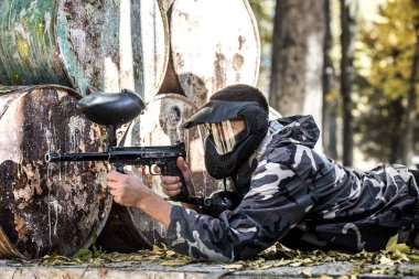 A man with a gun playing paintball.