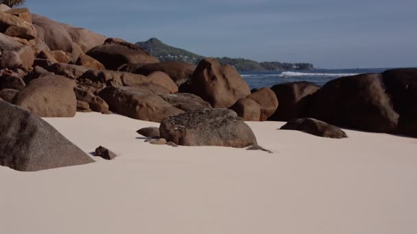 The ocean washes large stones on the shore of Seychelles
