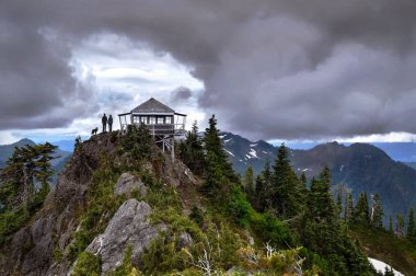 Couple with a dog standing on mountain top  by fire lookout hut under dramatic storm sky.
