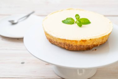 Homemade cheesecake  with mint on wood background