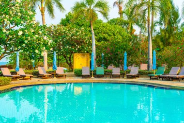 chair pool and umbrella around swimming pool with coconut palm tree - Holidays and vacation concept