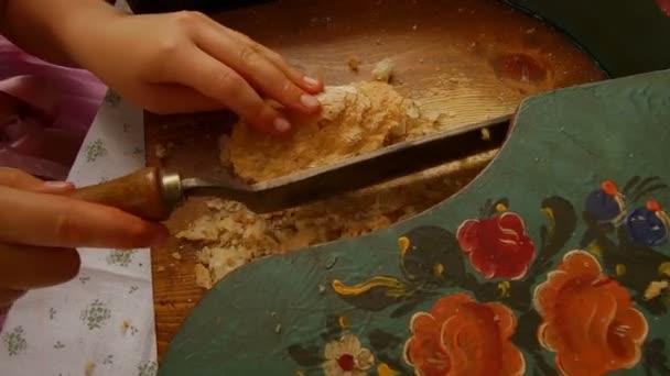 Detailaufnahme eines Jugendlichen in typischer Tiroler Tracht, der trockenes Brot mit typischem Tiroler Brotschnitt schneidet