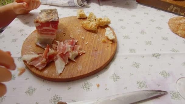 ein Jugendlicher im typischen Tiroler Kleid isst Speckscheiben