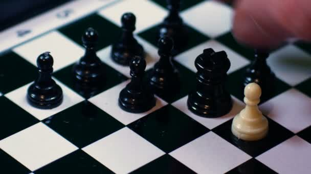 weiße Schachfigur wird von schwarzen Bauern umgeben, ideales Material, um Integrationsprobleme, Gewalt und Rassismus darzustellen