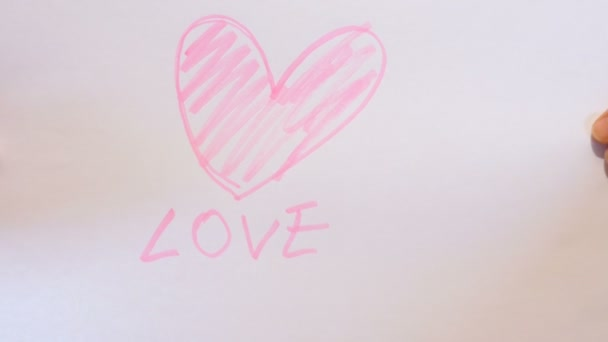 Teenage girl holds a paper sign in hand with a heart drawn over it, footage  to represent emotions of love and love affair