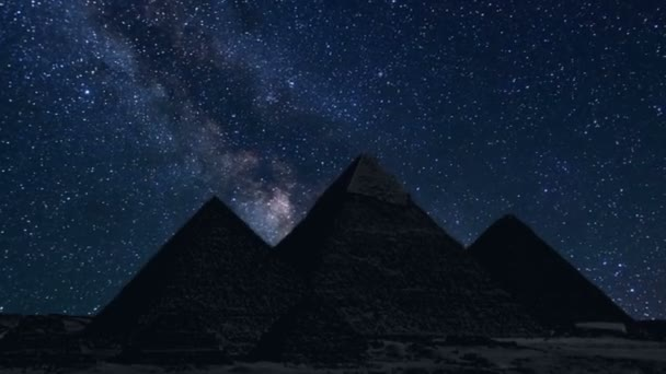 pyramids in silhouette with time lapse of stars