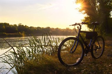Bicycle on the background of a calm forest lake