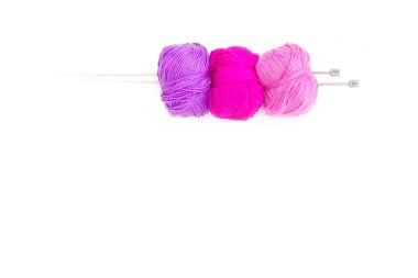 Color yarn is strung on knitting needles.