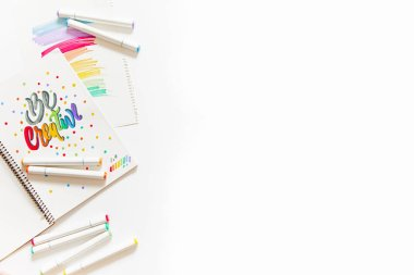 graphic design, handwriting, creation concept. tender little hands of female painter inscribing ornamental decorated letters on the white lined paper with Felt-tip pens