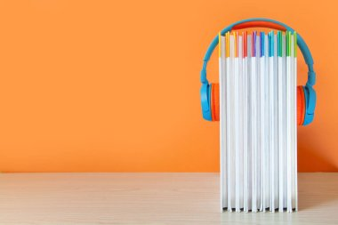 Colorful Headphones and books on color background. Concept of au