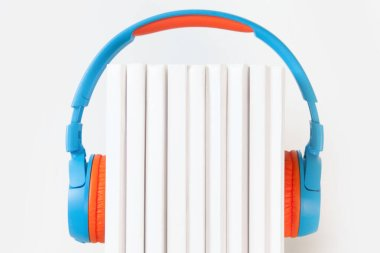 Colorful headphone and books on white background. Concept of aud