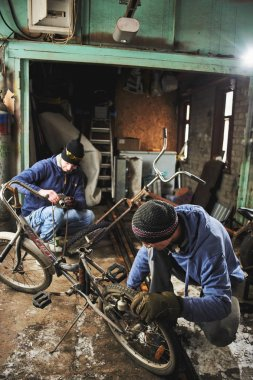 Men fixing bicycle parts while working in garage