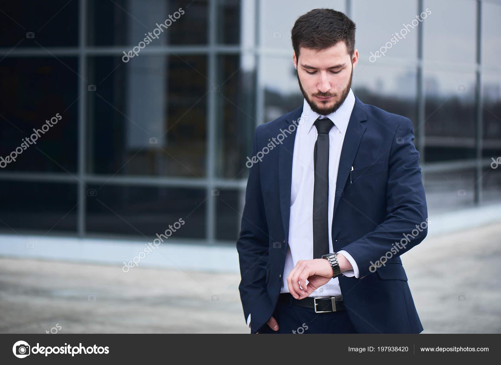 88db83b0b921 Όμορφος γενειοφόρος επιχειρηματία σε λευκό πουκάμισο και σακάκι βλέπουν  ρολόι από πλευρά ενώ στέκεται στο δρόμο — Εικόνα από ...