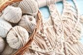 Fotografie makramé vlákna v koši na dřevěné pozadí, detail