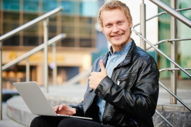 smiling blond businessman in leather jacket with laptop showing thumb up while sitting on porch of business center