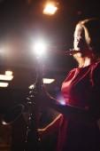 Fotografie Hudebník žena v červených šatech hrál saxofon na tmavém pódiu