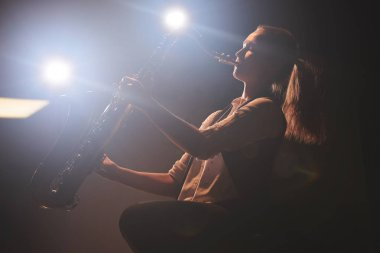 beautiful woman playing saxophone on stage