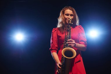 Musician woman in red dress playing saxophone on dark stage