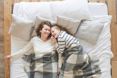 Mom and daughter lying in white bed among pillows at home