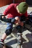 muž v kolečkové brusle sedí na schodech a utíral si ránu na kolena, koncept první lékařské pomoci