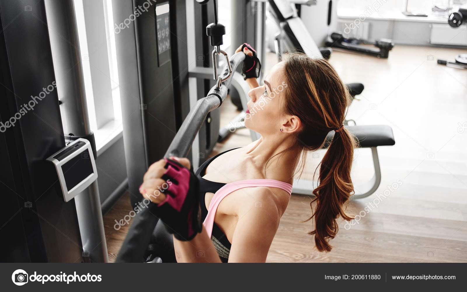 Bella donna utilizzando pulegge per tonificare i muscoli in palestra–  immagine stock f07baef94d9