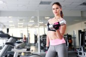 Fotografie attractive fitness woman lifting dumbbell in gym