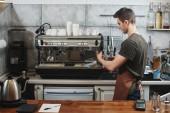 Fotografie gut aussehend Barista Schürze, Cappuccino mit Kaffeemaschine