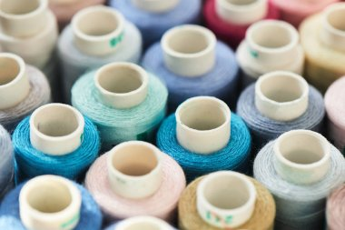 pile of bright fabric thread coils, close-up