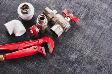 plumbing tools and equipment on a black shabby background closeup with copy space