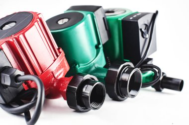 Red and green circulation pumps for heating on a white background.