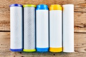 Water filters. Carbon cartridges on a wooden background. Household filtration system.