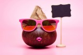 Il concetto di un turista vacanza nei paesi caldi, un viaggio in unisola tropicale, vacanze estive. Noce di cocco esotiche in occhiali da sole sta per viaggiare su uno sfondo rosa.