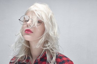 Portrait of a young beautiful blonde woman in round glasses and with plump lips in a red checkered shirt on a white background