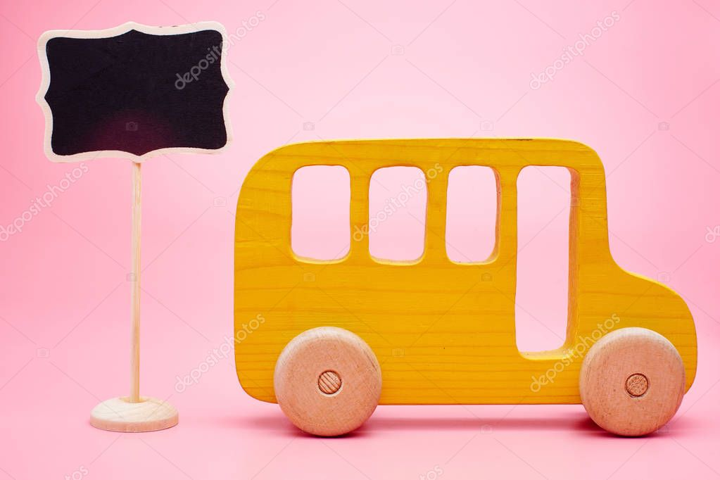 Yellow school bus with a copy space on a pink background. The concept of tourist recreation, travel, summer vacation, school start, the first of September