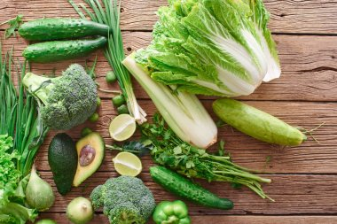 Fresh green vegetables and fruits and greens on a wooden background. Healthy eating concept