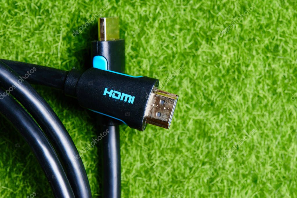 Black HDMI cable adapter connector on the background of green lawn