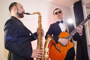 Group of two musicians, male jazz band, guitarist and saxophonist in classical costumes improvise on musical instruments in a studio stage lighting