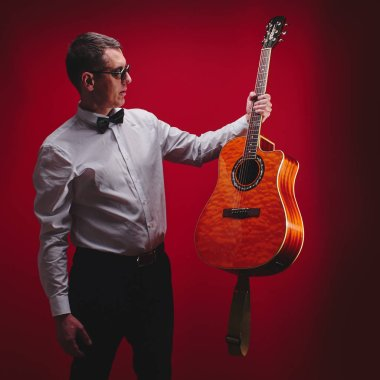 Portrait of classical musician with guitar in red studio. Guitarist in black glasses and a white shirt with a bow tie holds instrument in hand