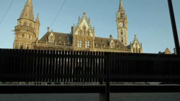 Fotoaparát se tyčí výložníku styl zpoza veřejné lavičce odhalit historické poštovní úřad a věž v náměstí Korenmarkt, Gent, považuje za východem slunce