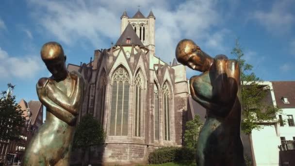 Kamera gleitet vorbei an De Fontein der Geknielden in Gent mit St.-Nikolaus-Kirche hinter