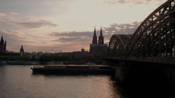 Statische Aufnahme der Hohenzollernbrücke und des Kölner Doms bei Sonnenuntergang in Deutschland. ein großer Kahn fährt unter Brücke durch
