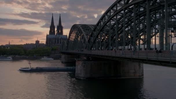 Statische Aufnahme der Hohenzollernbrücke und des Kölner Doms bei Sonnenuntergang in Deutschland, als Lastkähne unter Brücke durchfahren
