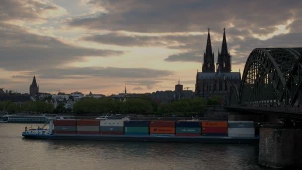 Kamera folgt Binnenschiff unter Hohenzollernbrucke mit Kölner Dom bei Sonnenuntergang in Deutschland