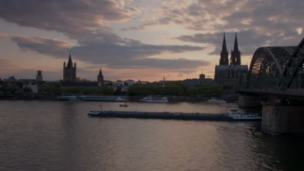 Pfanne zur Hohenzollernbrücke und zum Kölner Dom über den Rhein in Deutschland bei Sonnenuntergang, als Kahn darunter vorbeifährt