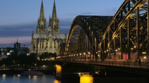 Statische Aufnahme der Hohenzollernbrücke und des Kölner Doms bei Nacht mit eingeschaltetem Licht. aufgenommen zur blauen Stunde
