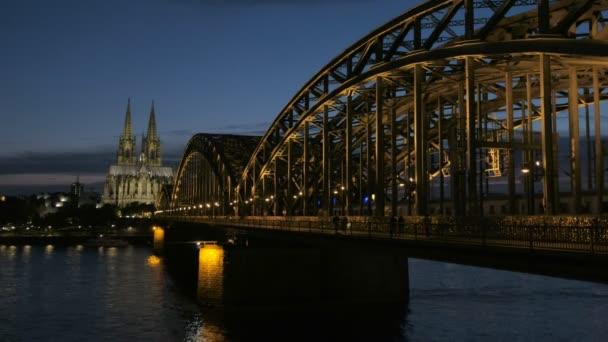 Statische Aufnahme der Hohenzollernbrücke und des Kölner Doms bei Nacht mit eingeschaltetem Licht. zur blauen Stunde, wenn der Zug durchfährt